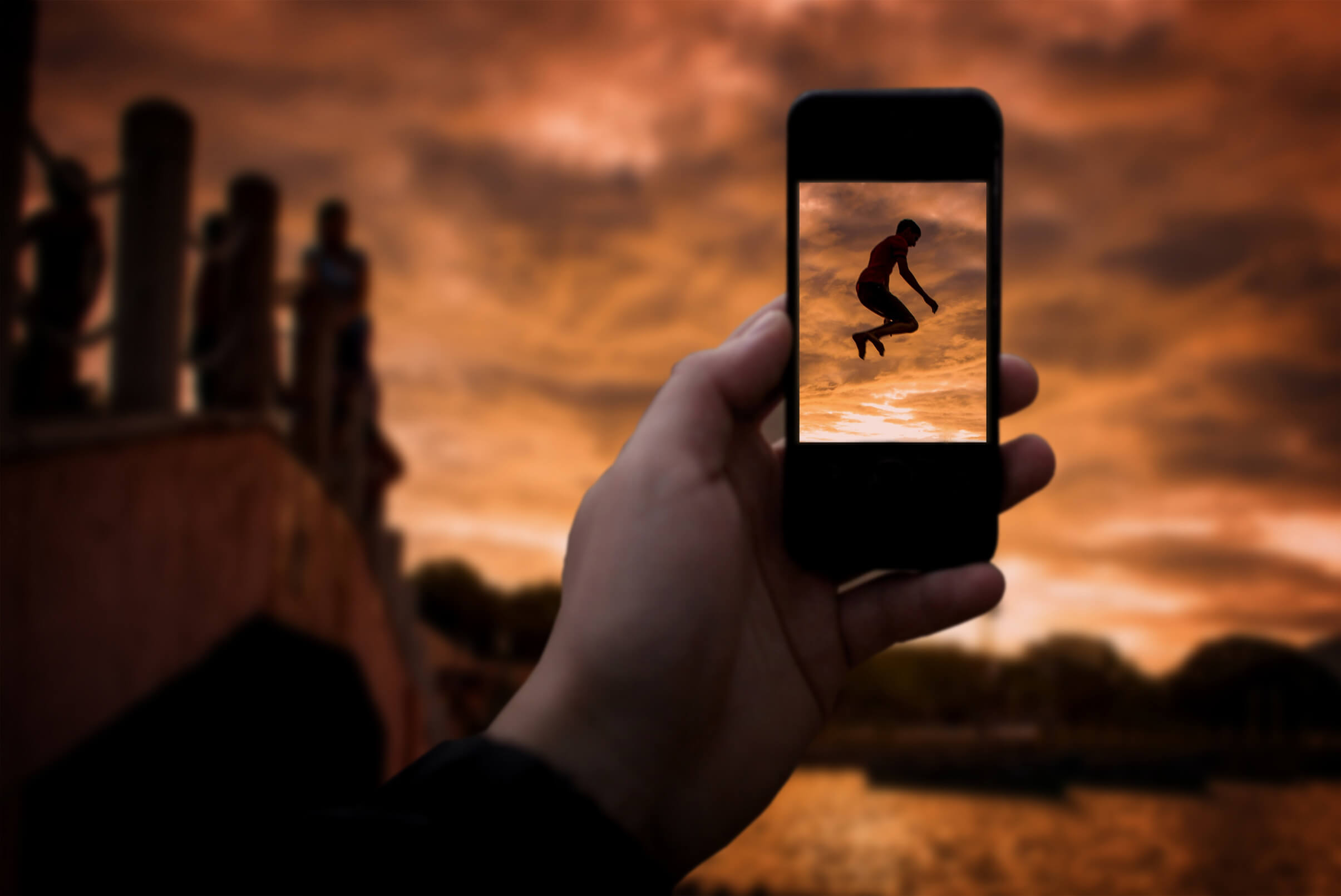 Taking a photo with smartphone - Happy boy jumping into river